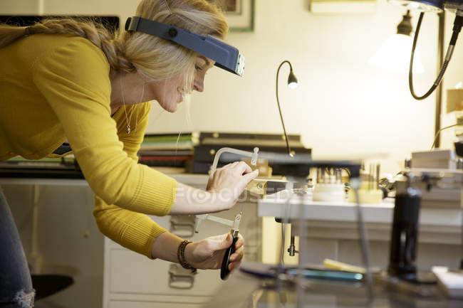 Fabricant féminin de bijoux utilisant la pince dans le studio de conception — Photo de stock