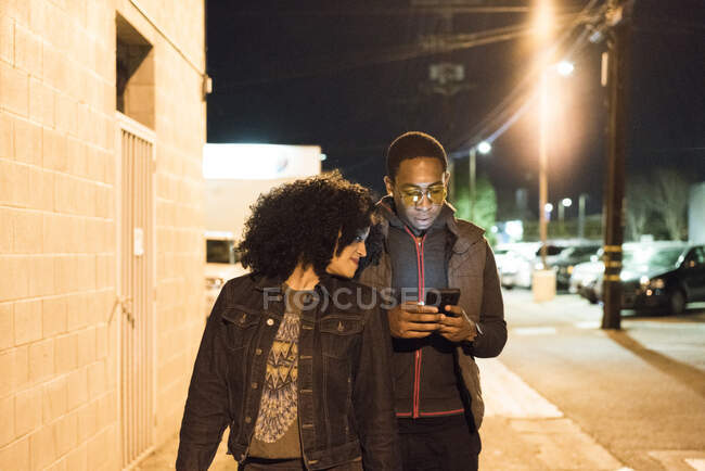 Couple walking in street at night looking at smartphone, Los Angeles, California, USA — Stock Photo