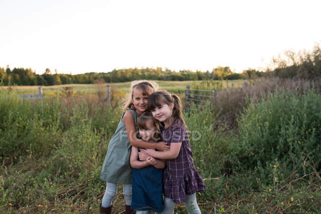 Retrato de tres chicas jóvenes de pie juntas en el campo, abrazándose - foto de stock