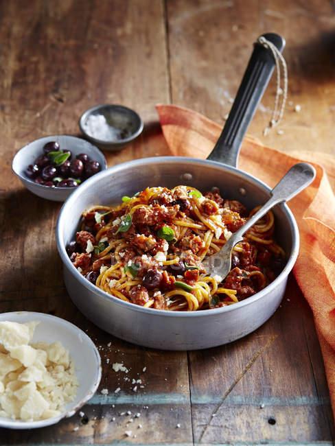 Spaghetti with italian sausage and ligurian olives — Stock Photo