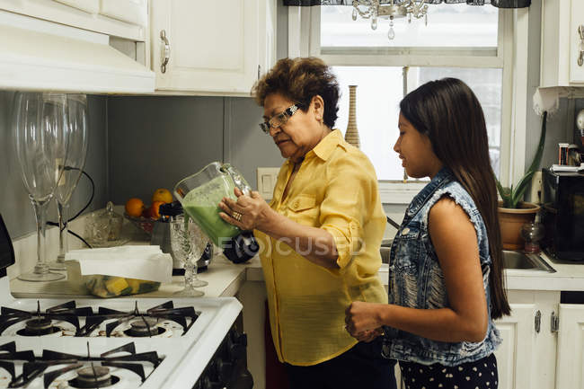 Grandmother and granddaughter preparing smoothies — Stock Photo