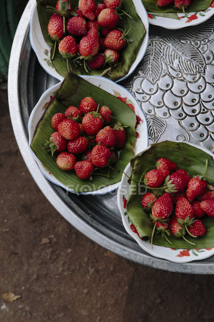 Top view of ripe strawberries on plates on table — Stock Photo