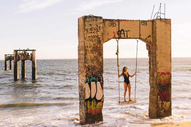 Femme debout sur la balançoire, Old Davenport Pier, Santa Cruz, Californie, USA — Photo de stock