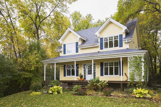 Amarelo clapboard com azul e branco guarnição casa estilo casa fachada no outono, Quebec, Canadá — Fotografia de Stock