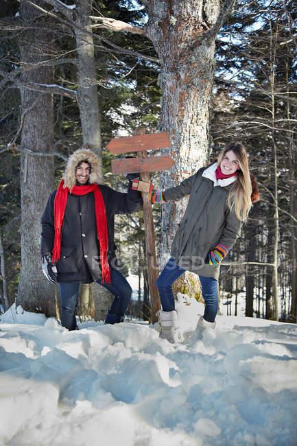 Coppia tenuta segno di legno nella foresta — Foto stock