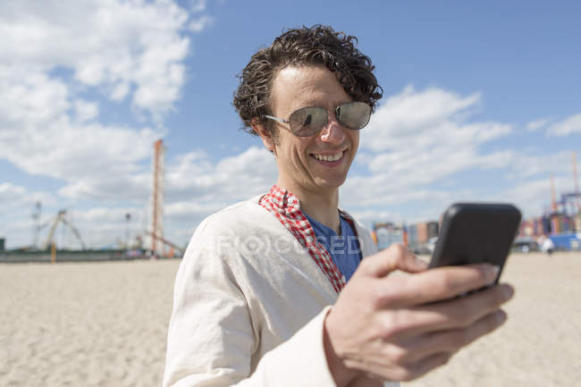 Mid adult man texting on smartphone at beach — Stock Photo