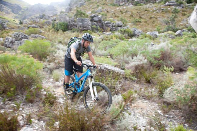 Jovem ciclismo de montanha através de matagal — Fotografia de Stock