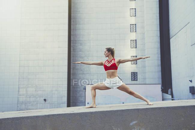 Молодая женщина на улице, стоящая на стене в положении йоги — стоковое фото