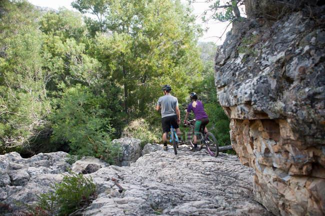 Jovem casal descansando em bicicletas de montanha em pedra — Fotografia de Stock