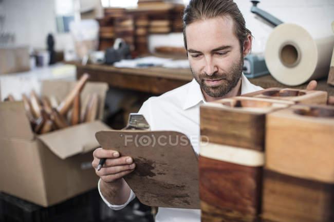 Человек с буфером обмена проверяет деревянные изделия на заводе — стоковое фото