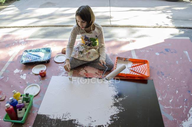 Chica en pintura de garaje con rodillo de pintura y cepillo - foto de stock