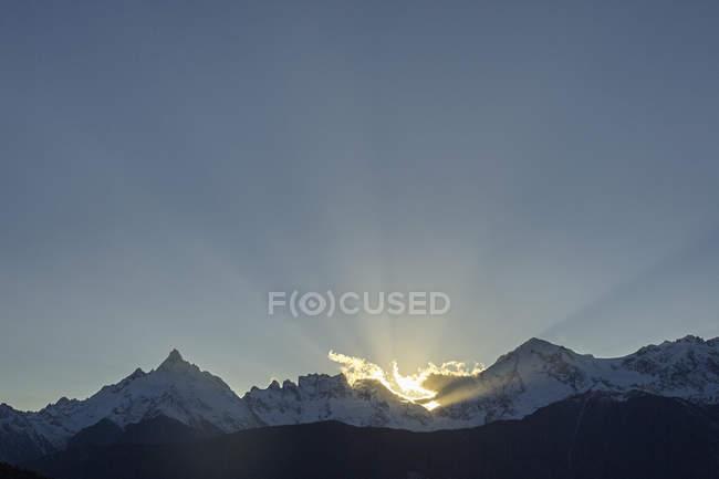 Raggi di sole dietro montagne innevate sotto il cielo blu — Foto stock