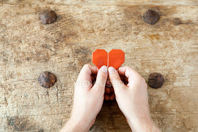 Person holding origami heart — Stock Photo