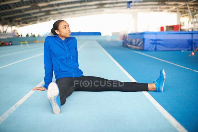 Jeune athlète féminine assis sur le sol qui s'étend de jambes — Photo de stock