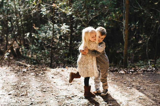 Fratelli che si abbracciano e giocano su strada sterrata — Foto stock