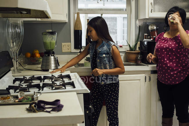 Mother and daughter in kitchen preparing smoothies — Stock Photo
