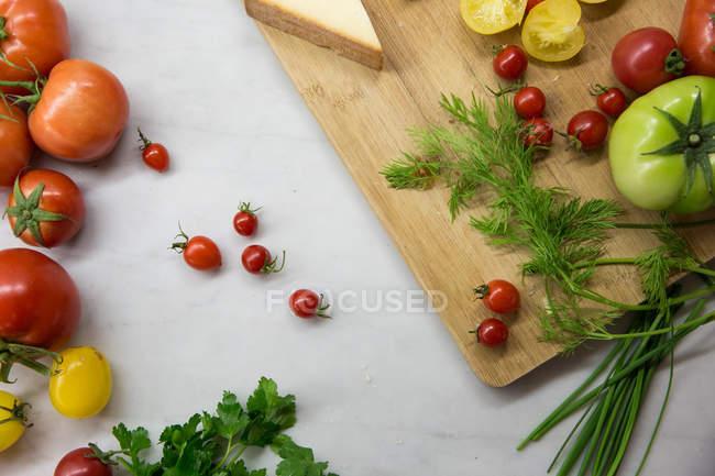 Вид сверху красные и зеленые помидоры на столе — стоковое фото
