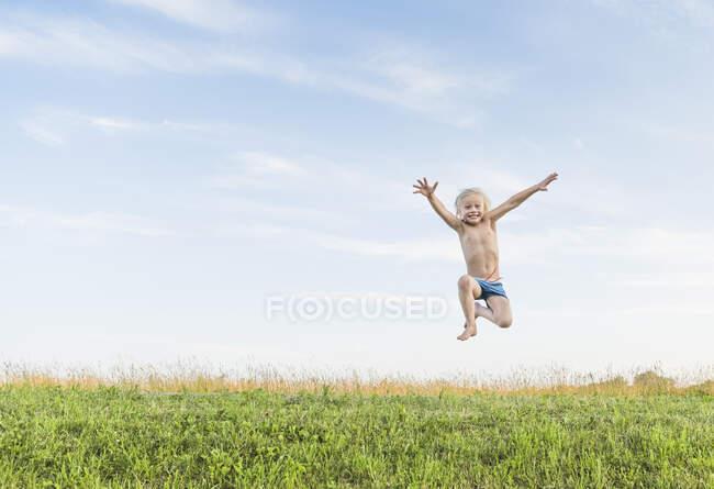 Хлопчик у польовому польоті стрибає в повітрі. — стокове фото