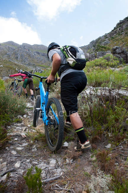 Rear view of young couple pushing mountain bikes up mountain path — Stock Photo