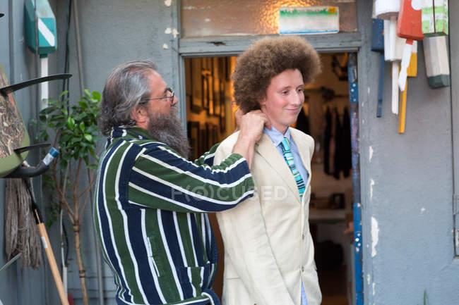 Зрілий чоловік, підлаштовуючий комірець для сина на вулиці. — стокове фото