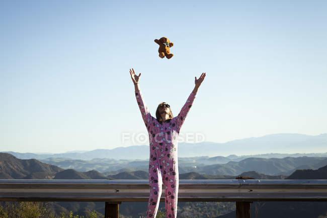 Homme portant une éponge rose lançant un ours en peluche en plein air, Malibu Canyon, Californie, États-Unis — Photo de stock