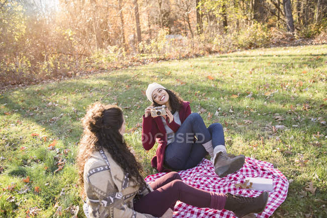 Young woman on picnic blanket photographing friend — Stock Photo