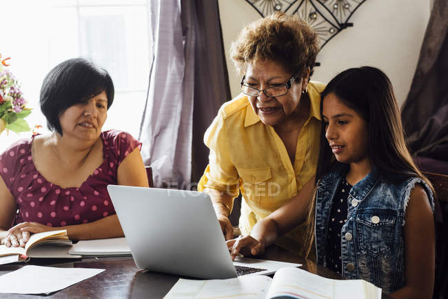Mother and grandmother helping girl with homework, using laptop — Stock Photo