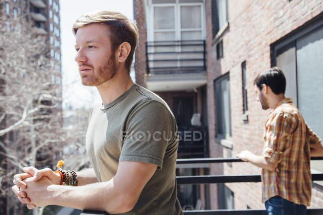 Мужская пара стоит на балконе, стоя вдали друг от друга, с грустным выражением лица — стоковое фото