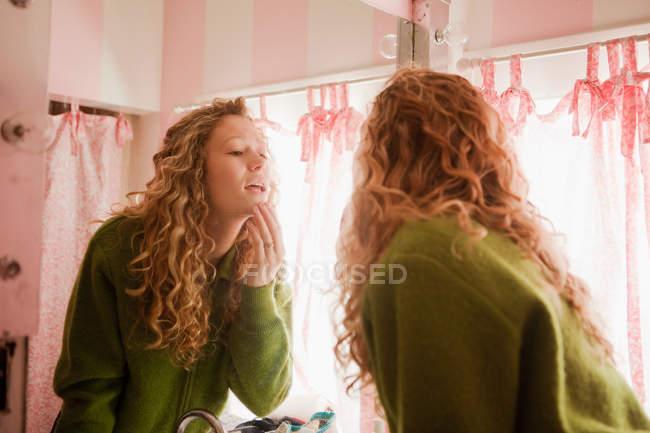 Teenage girl checking skin in bathroom mirror — Stock Photo