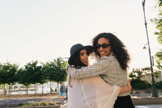 Portrait of two female mid adult friends looking over their shoulder on waterfront — Stock Photo