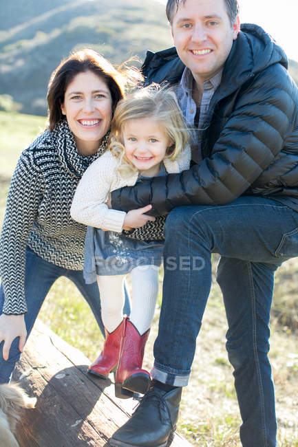 Portrait of mid adult couple and daughter on log — Stock Photo