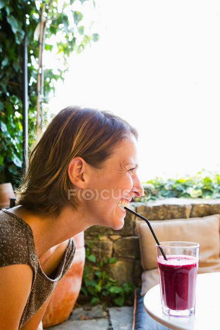 Woman drinking drink with straw — Stock Photo