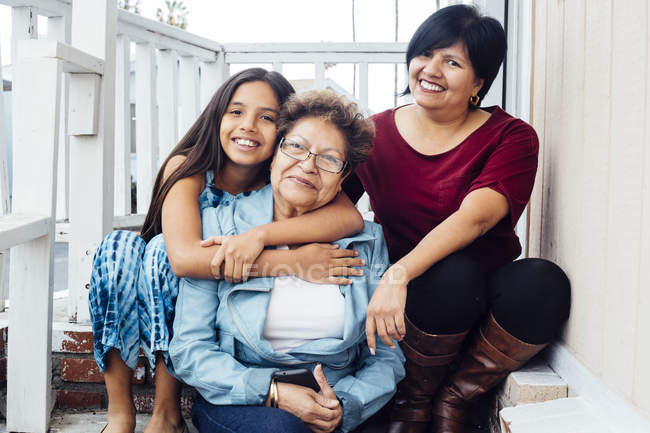 Portrait of multi generational family looking at camera and smiling — Stock Photo