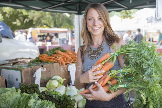 Mujer en puesto de frutas y verduras sosteniendo zanahorias - foto de stock