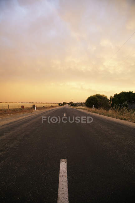 Diminishing view of marked road under sunset cloudy sky — Stock Photo