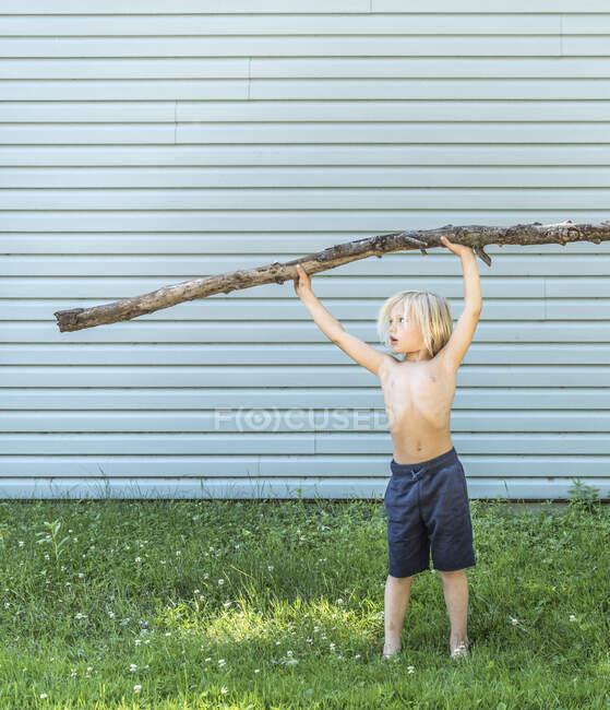 Ragazzo con braccia alzate bastone — Foto stock