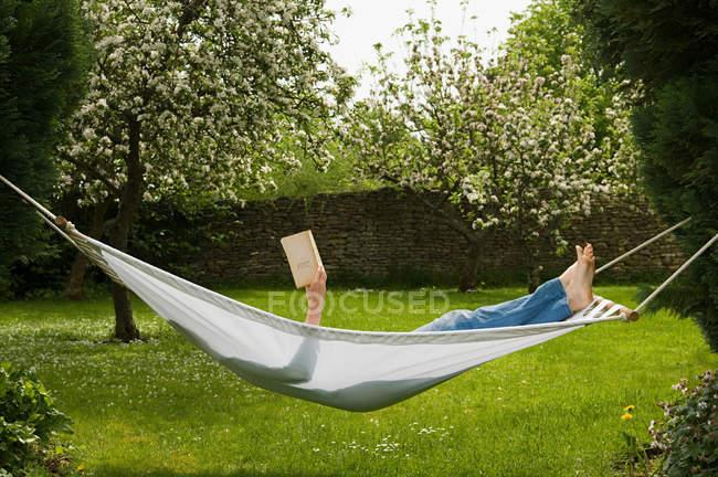 Mujer leyendo libro mientras que miente en hamaca - foto de stock