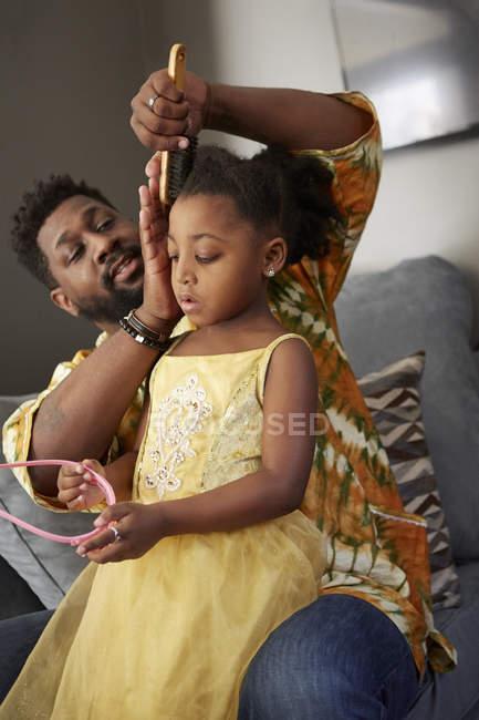 Мужчина на диване расчесывает дочери волосы для принцессы Тиары — стоковое фото