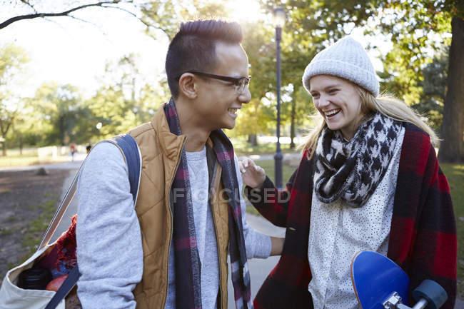Молодая женщина-скейтбордистка смеется с парнем в парке — стоковое фото