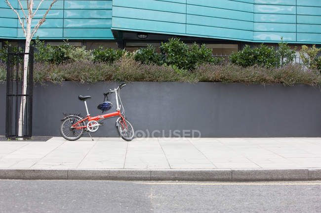 Children Bicycle with helmet parked on sidewalk — Stock Photo