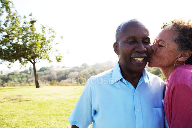 Старшая женщина целует мужчину в щеку — стоковое фото