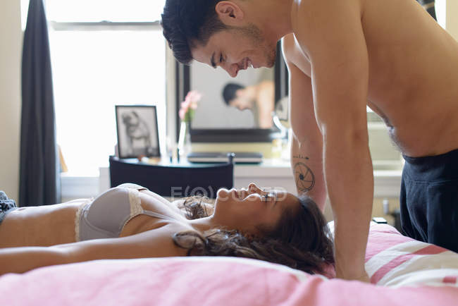 Young couple in bed, woman lying on back with man above — Stock Photo