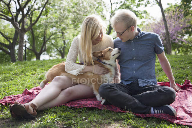 Young couple with corgi dog sitting in park — Stock Photo