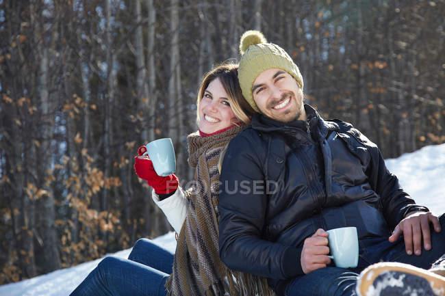 Ritratto di coppia seduta sulla neve con bevande calde — Foto stock