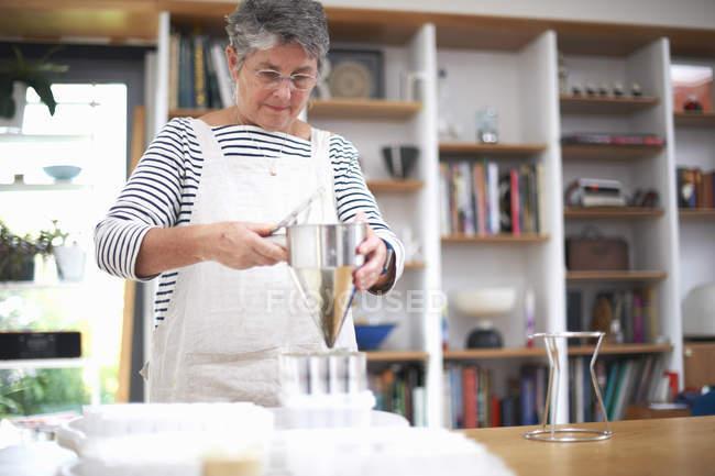 Старшая женщина использует блинную воронку, чтобы залить смесь в пластиковые горшки — стоковое фото