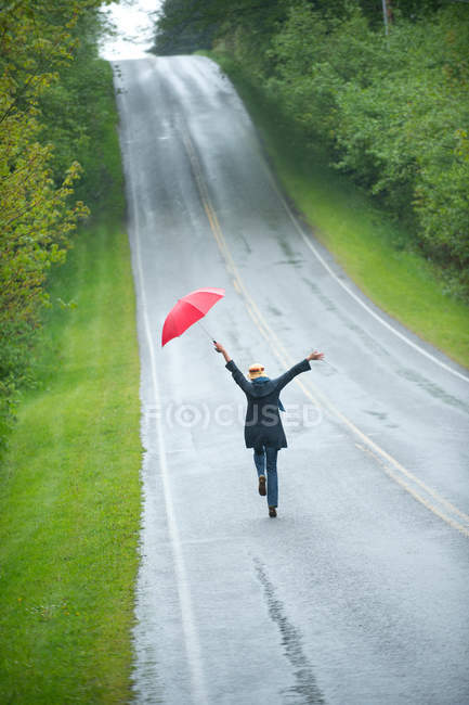 Rear view of woman on empty road with red umbrella — Stock Photo