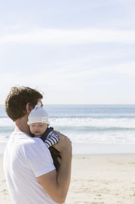 Père retenant le bébé, à la plage — Photo de stock