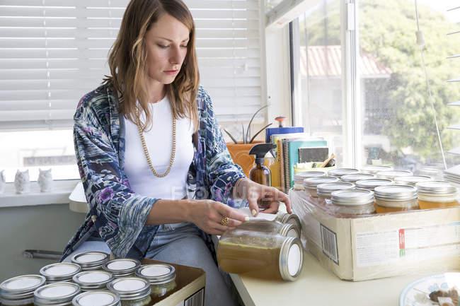 Mujeres etiquetando tarros en casa - foto de stock