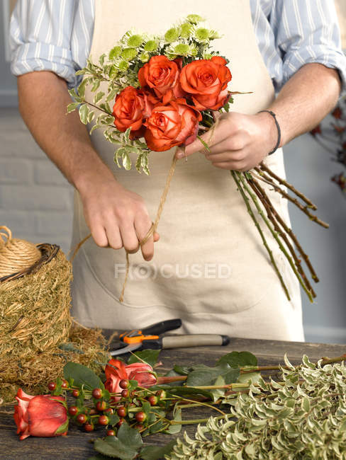 Cropped image of Florist tying bouquet in shop — Stock Photo
