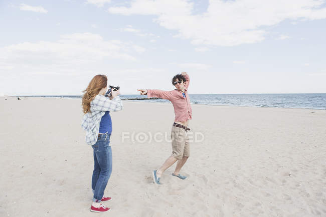 Couple photographing with instant camera on beach — Stock Photo